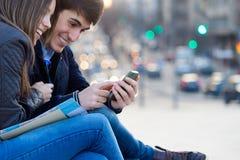 Unga par av turisten i stad genom att använda mobiltelefonen Arkivbild