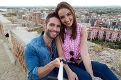 Unga par av turisten i stad genom att använda mobiltelefonen Fotografering för Bildbyråer