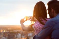 Unga par av turisten i stad genom att använda mobiltelefonen Arkivfoton