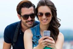 Unga par av turisten i stad genom att använda mobiltelefonen Arkivfoto