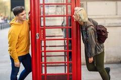 Unga par av vänner nära ett klassiskt brittiskt rött telefonbås arkivfoton