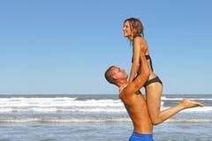Unga par av vänner som har gyckel i havet på en strandferie Arkivfoto
