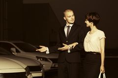 Unga par för modeaffär som samlar den nya bilen på återförsäljare l Royaltyfria Bilder