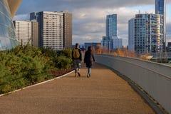 Unga par går i drottningen Elizabeth Olympic Park fotografering för bildbyråer