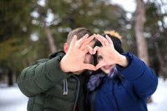 Unga par gör hjärtaform vid fingrar arkivfoto