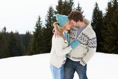 Unga par i alpin Snowplats Royaltyfri Bild