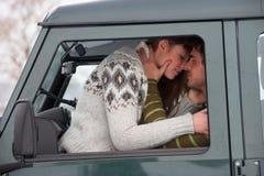 Unga par i bil i snow Arkivfoto