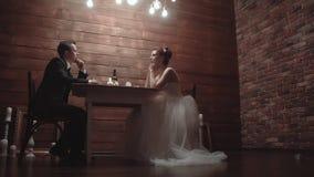 Unga par i en gifta sig dress som sitter i en restaurang och talar, under matst?lle l?ngsam r?relse arkivfilmer