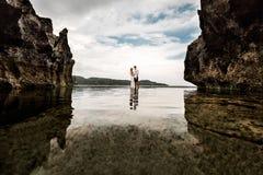 Unga par i havslilla viken mellan klipporna royaltyfria foton