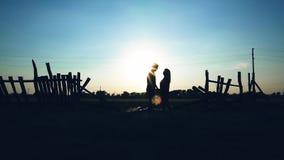 Unga par i lyoungpar som är förälskade utanför staden i natur på sunsetove utanför staden i natur på solnedgången lager videofilmer