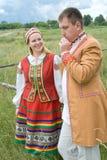 Unga par i nationell belarusian kläder. Arkivfoto