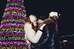 Unga par i vinterpälskläder som kramar under chimes på julnatt arkivfoton