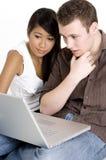 Unga par med bärbar dator royaltyfri foto