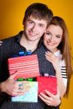 Unga par med gåvor på yellow Royaltyfri Foto