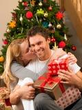 Unga par med gåvor som är främre av julgran Arkivfoto