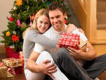 Unga par med gåvor som är främre av julgran Royaltyfria Bilder