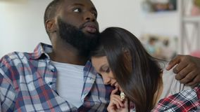 Unga par med hållande ögonen på fasafilm för spänning och för skräck och ätapopcorn arkivfilmer