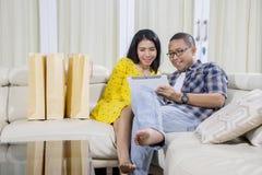 Unga par med minnestavlan och pappers- påsar arkivfoto
