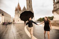 Unga par med paraplyet som g?r i Budapest p? en regnig dag k?rlekshistoria f?r tr?dg?rds- flicka f?r pojke kyssande royaltyfri fotografi