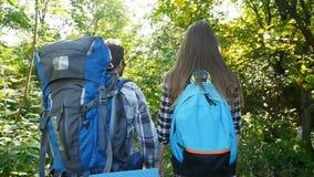 Unga par med ryggsäckar i skogloppet och fotvandrabegreppet arkivfilmer