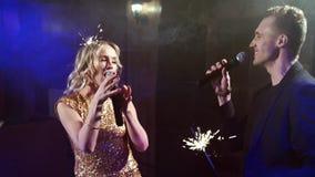 Unga par med tomtebloss som dansar och sjunger i en nattklubb arkivfilmer