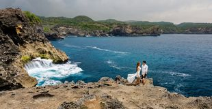 Unga par på en klippa vid havet fotografering för bildbyråer