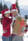 Unga par på snowen med julgåvan royaltyfri fotografi