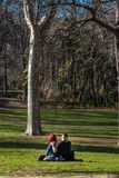 Unga par som är förälskade på gräset i ett utomhus-, parkerar arkivbilder