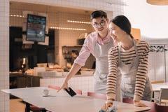 Unga par som arbetar deltids- jobb som uppassare i restaurangen arkivbild