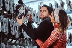 Unga par som bär varm kläder som står nära kuggen med många par av skridskor som väljer hans format royaltyfri bild