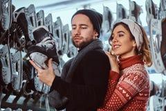 Unga par som bär varm kläder som står nära kuggen med många par av skridskor som väljer hans format royaltyfria foton