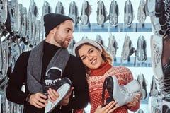 Unga par som bär varm kläder som står nära kuggen med många par av skridskor som väljer hans format arkivbild