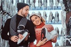 Unga par som bär varm kläder som står nära kuggen med många par av skridskor som väljer hans format arkivfoton