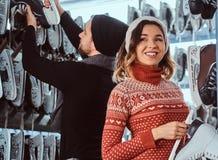 Unga par som bär varm kläder som står nära kuggen med många par av skridskor som väljer hans format arkivbilder