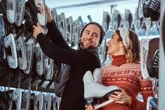 Unga par som bär varm kläder som står nära kuggen med många par av skridskor som väljer hans format arkivfoto