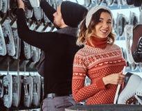 Unga par som bär varm kläder som står nära kuggen med många par av skridskor som väljer hans format fotografering för bildbyråer