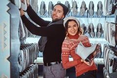 Unga par som bär varm kläder som står nära kuggen med många par av skridskor som väljer hans format royaltyfri foto