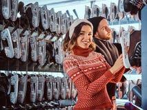 Unga par som bär varm kläder som står nära kuggen med många par av skridskor som väljer hans format royaltyfria bilder
