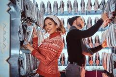 Unga par som bär varm kläder som står nära kuggen med många par av skridskor som väljer hans format royaltyfri fotografi