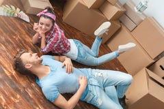 Unga par som flyttar sig till liggande talande le för nytt ställe som är lyckligt royaltyfria bilder