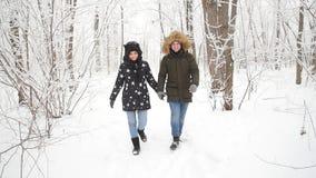 Unga par som går i den snöig skogen arkivfilmer
