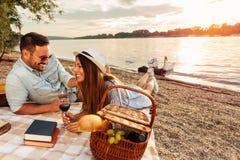 Unga par som har en picknick på stranden Ligga på picknickfilten som dricker rött vin arkivbild