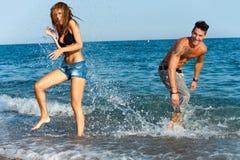 Unga par som har gyckel med vatten. Arkivfoto
