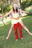 Unga par som har gyckel tillsammans i trädgård Fotografering för Bildbyråer