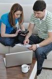 Unga par som hemma fungerar på bärbar dator royaltyfria foton