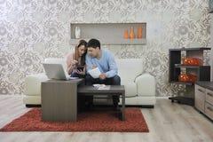 Unga par som hemma fungerar på bärbar dator royaltyfria bilder