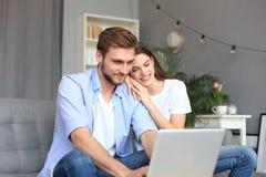 Unga par som hemma gör någon online-shopping, genom att använda en bärbar dator på soffan royaltyfria bilder