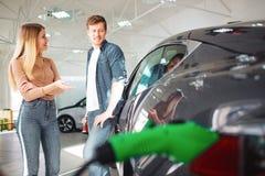Unga par som köper en första elbil i en visningslokal Diskussion om betalning Modern teknologi i det automatiskt arkivbild