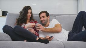 Unga par som kopplar av i deras lägenhet, ligger på soffan och håller ögonen på filmen arkivfilmer