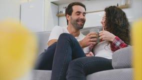 Unga par som kopplar av i deras lägenhet, ligger på soffan och håller ögonen på filmen stock video